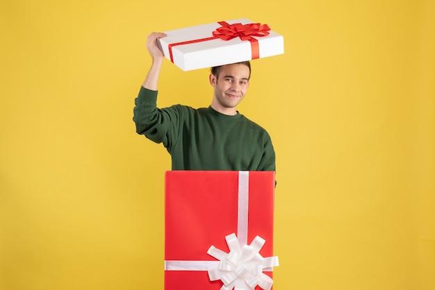 Vue de face jeune homme mettant le couvercle de la boîte sur sa tête debout derrière un grand coffret sur jaune