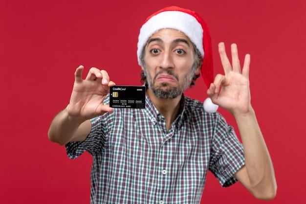 Vue de face jeune homme montrant une carte bancaire sur fond rouge