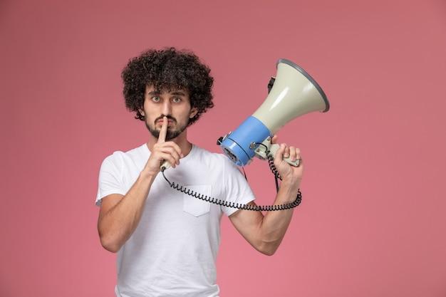 Vue de face jeune homme montrant garder le geste silencieux avec microphone à main