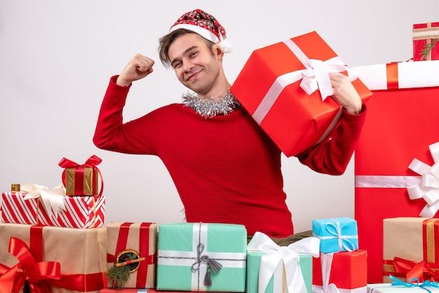 Vue de face jeune homme montrant des muscles assis autour de cadeaux de noël