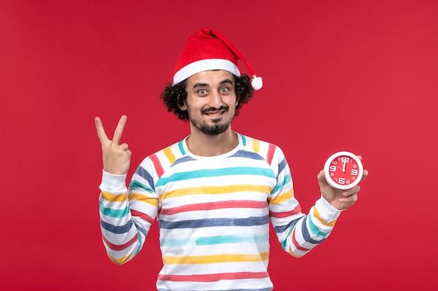Vue de face jeune homme montrant le nombre sur le mur rouge temps nouvel an vacances mâle rouge