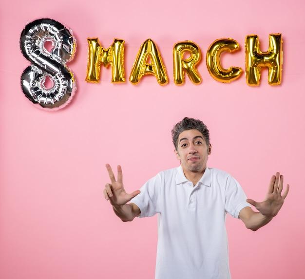 Vue de face jeune homme montrant le numéro avec décoration de mars sur fond rose égalité émotion couleur vacances womens day partie modèle