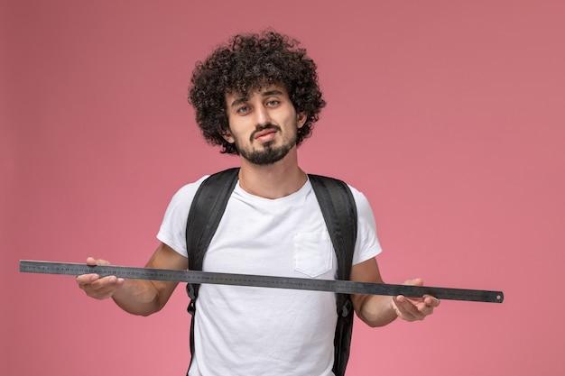 Vue de face jeune homme montrant une règle pour l'éducation
