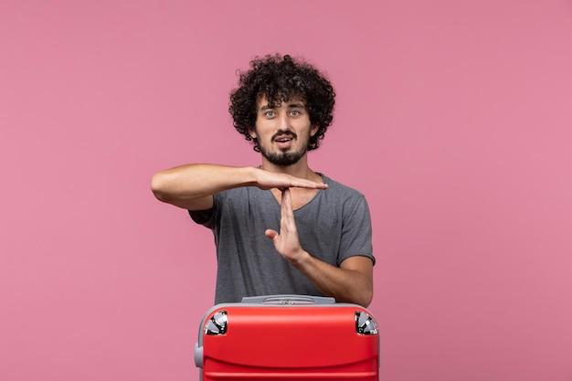 Vue de face jeune homme montrant le signe t sur l'espace rose