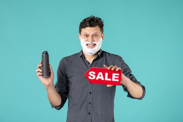 Vue de face jeune homme avec de la mousse sur son visage tenant la plaque signalétique de vente sur fond bleu