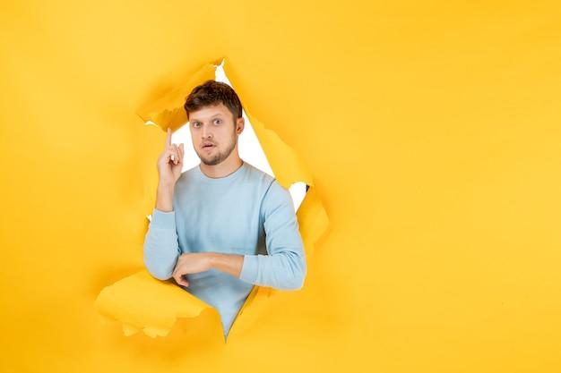 Vue de face jeune homme sur mur déchiré jaune