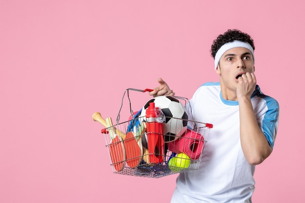 Vue de face jeune homme nerveux en vêtements de sport avec panier plein de choses sportives