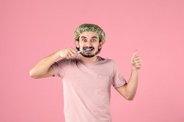 Vue de face jeune homme nettoyant ses dents sur fond rose