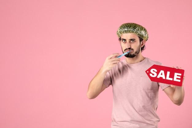 Vue de face jeune homme nettoyant ses dents et plaque signalétique de vente sur fond rose