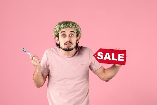 Vue de face jeune homme nettoyant ses dents et tenant la plaque signalétique de vente sur fond rose
