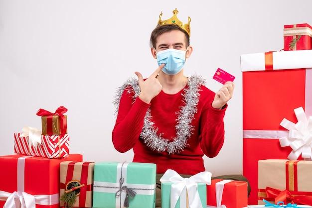 Vue de face jeune homme de noël avec masque tenant la carte assis sur les cadeaux de noël de plancher