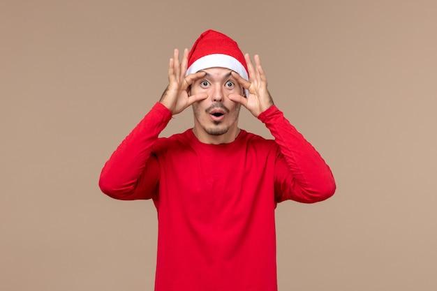 Vue de face jeune homme ouvrant les yeux sur fond marron émotion vacances de noël