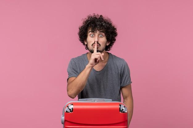 Vue de face jeune homme partant en vacances avec son sac rouge sur l'espace rose