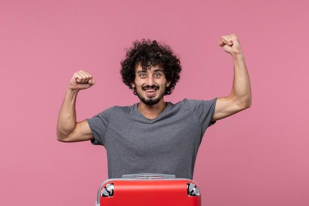 Vue de face jeune homme partant en vacances avec son sac rouge se sentant heureux sur un espace rose