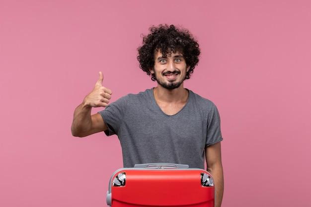 Vue de face jeune homme partant en vacances avec son sac rouge souriant sur un espace rose