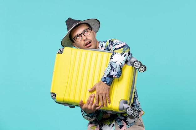 Vue de face jeune homme partant en vacances et tenant son sac sur l'espace bleu
