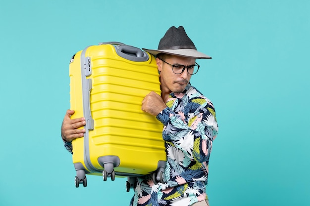 Vue de face jeune homme partant en vacances et tenant son sac jaune sur l'espace bleu clair