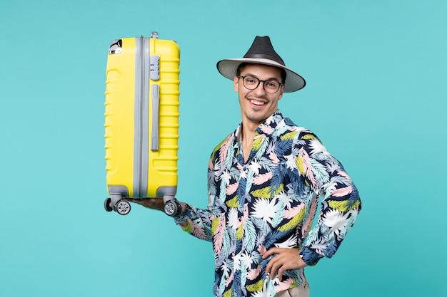 Vue de face jeune homme partant en vacances et tenant son sac jaune sur l'espace bleu