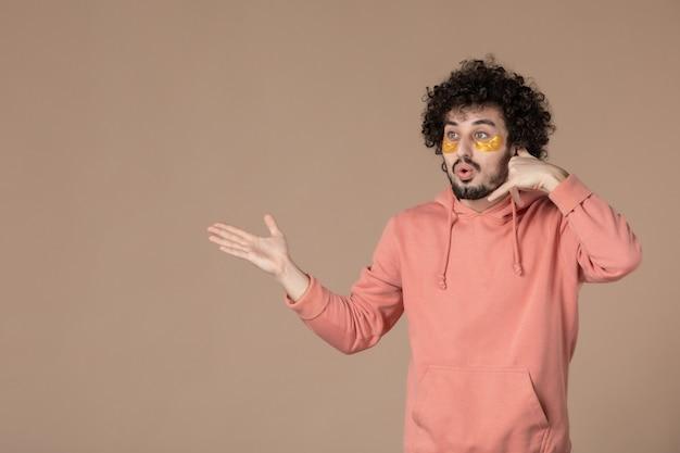 Vue de face jeune homme avec des patchs oculaires imitant un appel téléphonique sur fond marron crème de massage soin du visage spa de la peau