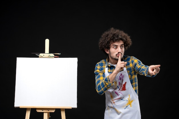 Vue de face jeune homme peintre avec chevalet sur tableau noir
