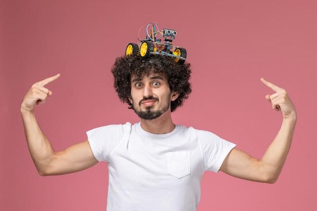 Vue de face jeune homme pointant l'artuino électronique sur sa tête