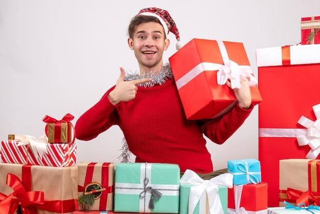 Vue de face jeune homme pointant sur boîte-cadeau assis autour de cadeaux de noël