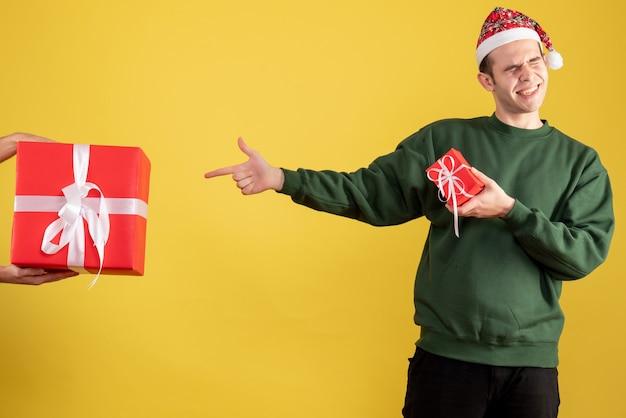 Vue de face jeune homme pointant sur le cadeau en main féminine sur jaune