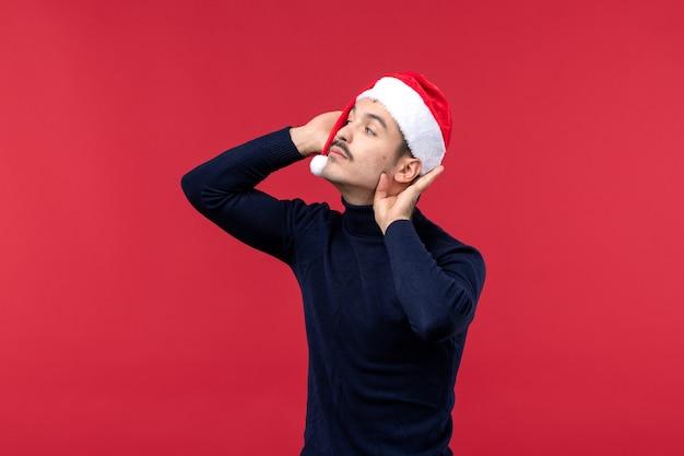 Vue de face jeune homme portant une casquette de nouvel an sur le fond rouge