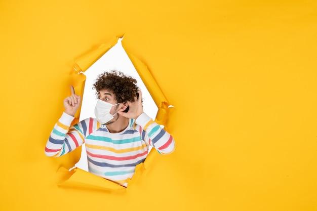 Vue de face jeune homme portant un masque stérile écoutant sur une photo de virus pandémique humain de couleur jaune covid-health