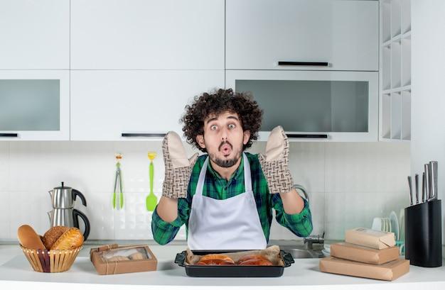 Vue de face d'un jeune homme portant un support debout derrière une table de pâtisseries fraîchement cuites dessus dans la cuisine blanche