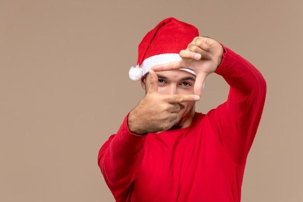Vue de face jeune homme posant sur fond marron émotion vacances de noël