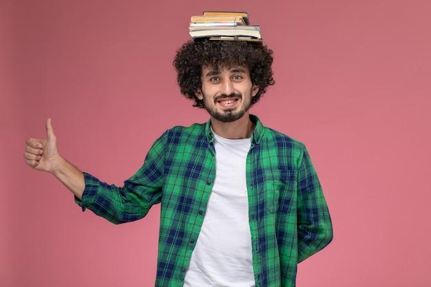 Vue de face jeune homme posant tandis que les livres sont sur sa tête
