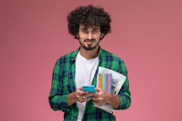 Vue de face jeune homme posant avec téléphone portable et ordinateurs portables sur fond rouge