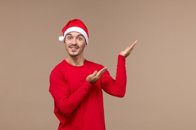 Vue de face jeune homme posant avec visage excité sur fond marron émotions vacances noël