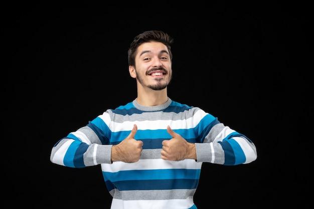 Vue de face jeune homme avec les pouces vers le haut
