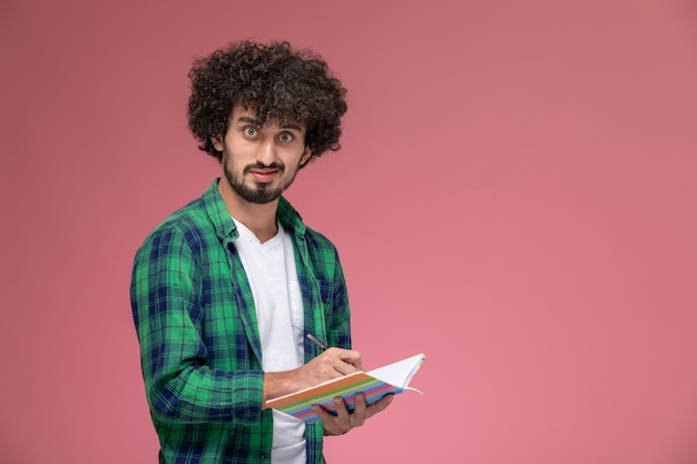 Vue de face jeune homme prenant des notes et regardant la caméra