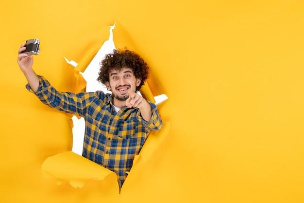 Vue de face jeune homme prenant une photo avec un appareil photo sur fond jaune
