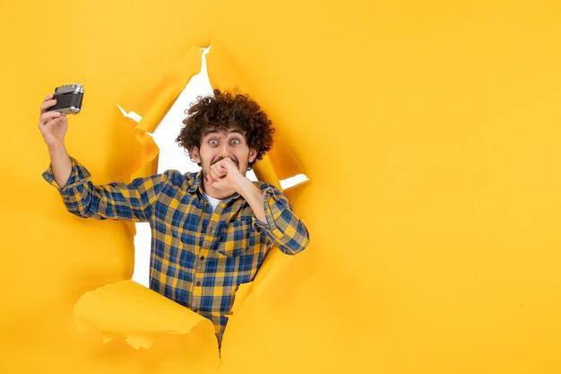 Vue de face jeune homme prenant une photo de selfie avec appareil photo sur fond jaune