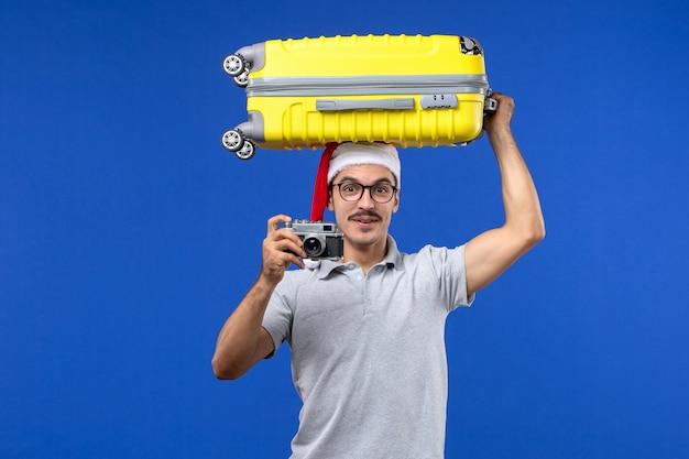 Vue de face jeune homme prenant la photo et tenant le sac sur l'avion de vacances de vols de mur bleu