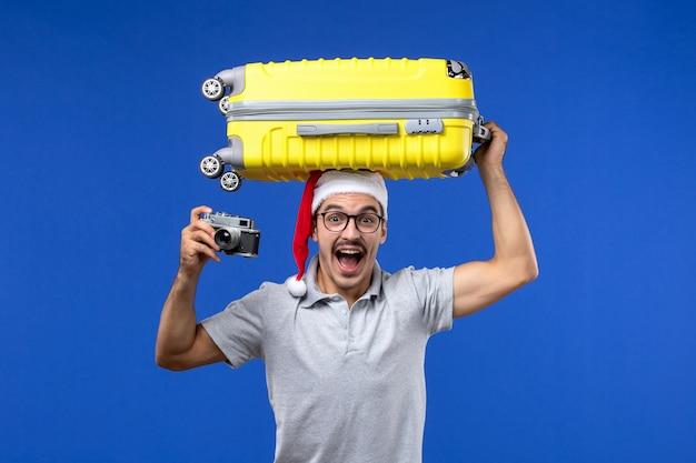 Vue de face jeune homme prenant la photo et tenant le sac sur les avions de vacances vols mur bleu