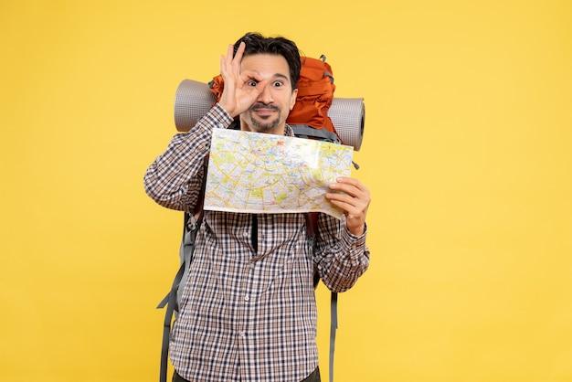 Vue de face jeune homme prépare pour la randonnée tenant la carte sur jaune