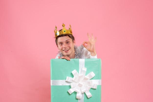 Vue de face jeune homme présent à l'intérieur avec couronne sur bureau rose