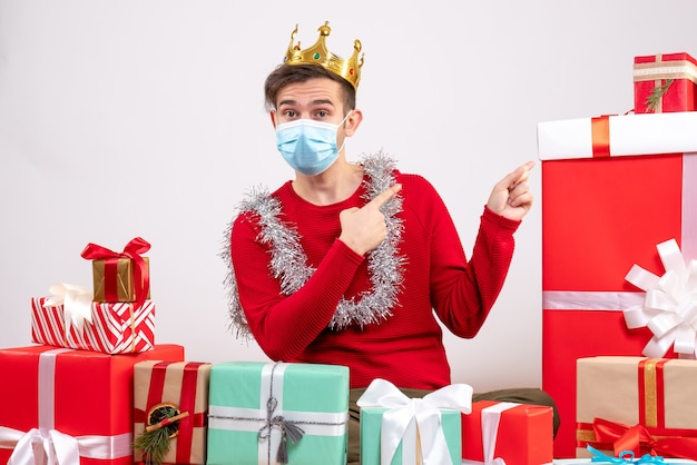 Vue de face jeune homme avec pull rouge assis sur des cadeaux de noël de plancher