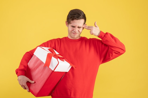 Vue de face jeune homme avec pull rouge mettant le pistolet à doigt à sa tempe sur fond jaune
