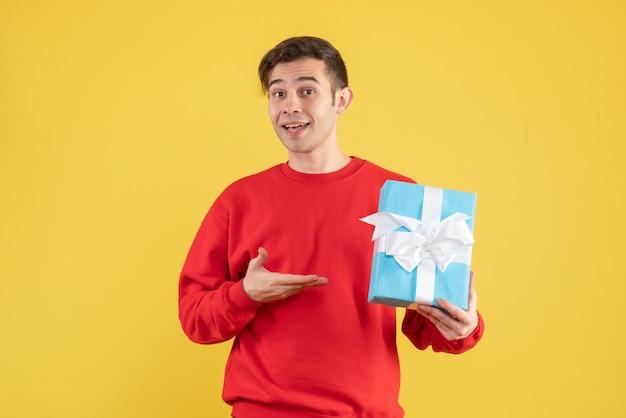 Vue de face jeune homme avec pull rouge montrant son cadeau sur fond jaune