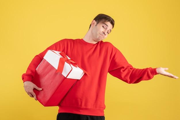 Vue de face jeune homme avec pull rouge ouvrant sa main sur fond jaune