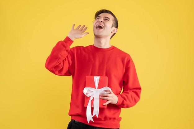 Vue de face jeune homme avec pull rouge à la recherche sur fond jaune