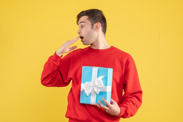 Vue de face jeune homme avec pull rouge tenant une boîte cadeau bleue sur fond jaune