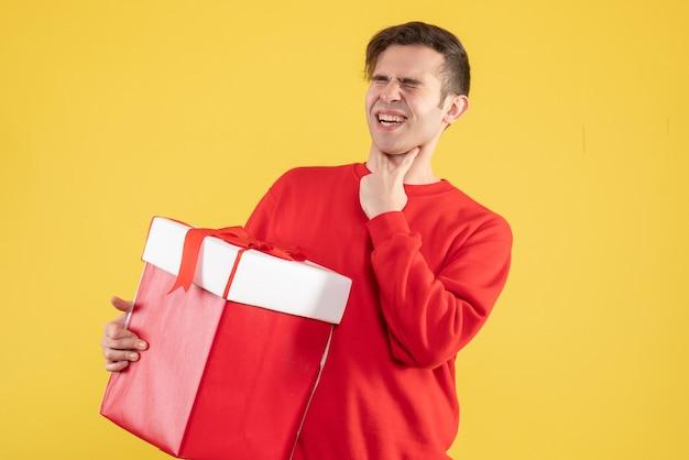 Vue de face jeune homme avec pull rouge tenant la gorge sur fond jaune