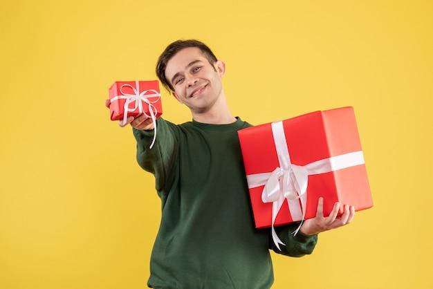 Vue de face jeune homme avec pull vert donnant un cadeau de noël debout sur jaune